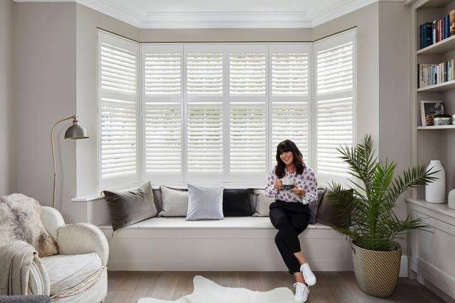 Anna Richardson sat in a white decorated living room with a bay window that has tiered silk white shutters