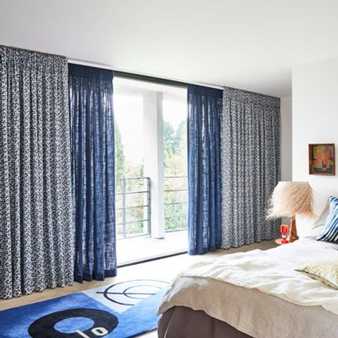 Bedroom with wide floor to ceiling windows dressed with funky printed blue and white curtains layered on dark blue curtains and cushions to match on the bed