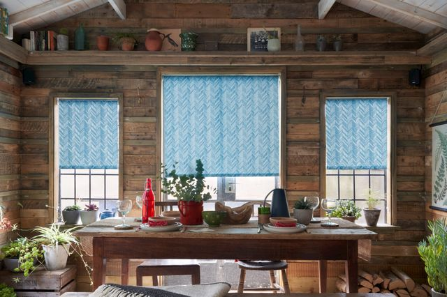 Patterned blue Roller blinds in 3 windows side by side in a wooden, rustic dining room