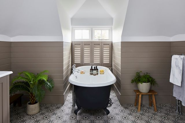Beige shutters matching with the wall colour, behind a bath, funky tiled floor and plants beside the bath