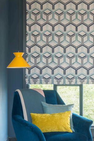 Geometric teal roman blind in large window with teal velvet armchair and mustard lampshade and cushion