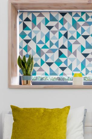 Blue geometric perfect fit roller blind in bedroom with house plant on window ledge