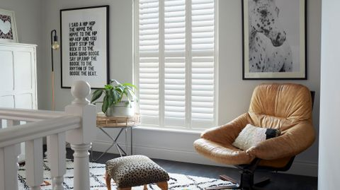 Silk white full height shutters on landing with large leather armchair, leopard print foot stool and house plant