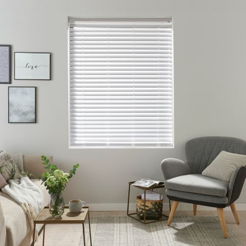 White wooden style venetian blind with grey armchair and small, modern gallery on the wall