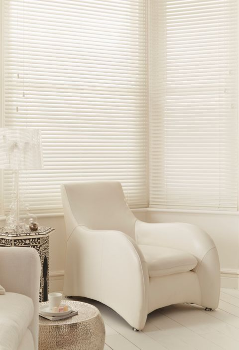 White wooden venetian blind in a bay window with white leather armchair and mirrored mosaic-mirror style side table