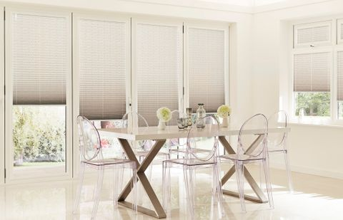 Grey ombre pleated conservatory side blinds with large dining table and 6 clear Perspex chairs surrounding