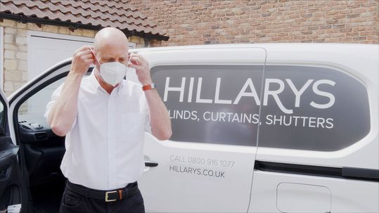 A Hillarys advisor putting on a face mask next to a van before entering a customers home