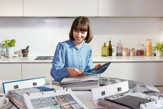 Brunette haired lady looking through samples of fabrics in the kitchen of home