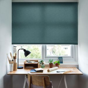 A small office space with the Battersea Peacock Roller blind freely hanging in a window above the desk. The jacquard design is set against neutrally decorated walls.
