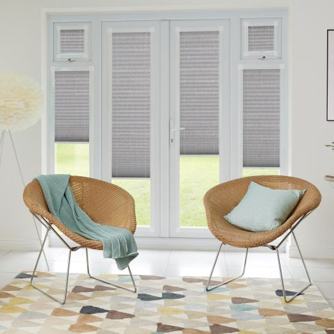 Grey pleated perfect fit blinds in patio door windows with light rattan style desk chairs with dug egg blue accessories