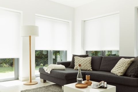 White hexham roller blind in large living room windows with grey sofa and wooden floor lamp