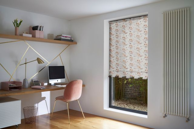 home office with orange and cream patterned blind with pink desk chair and gold accessories