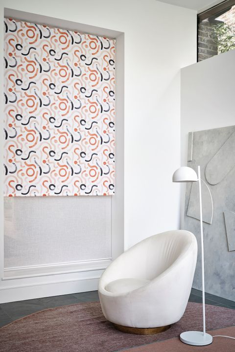 A relaxed grey and white space, with a white, light pink, orange and blue patterned blind