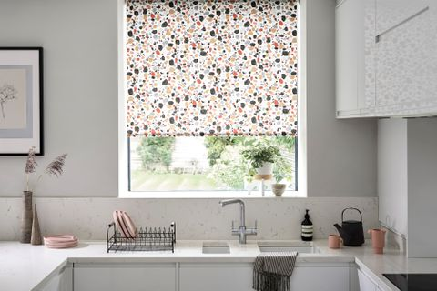 Marble kitchen with a white, blue, yellow, red and black patterned blind and warm accessories