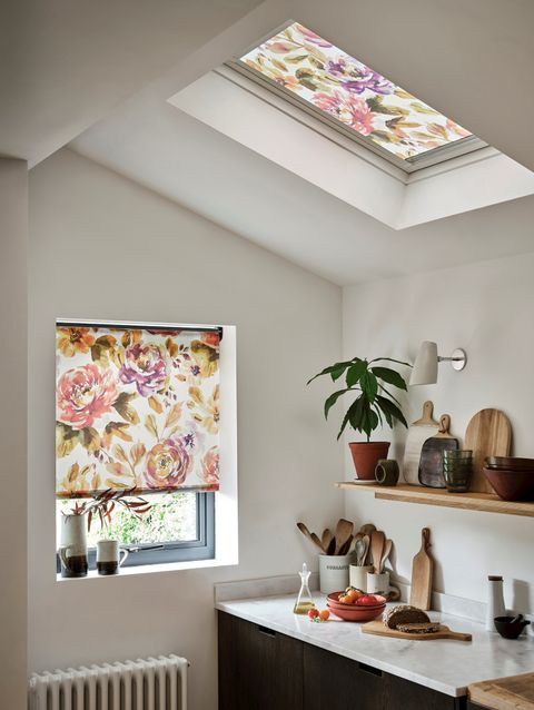 Marble kitchen with a floral blind and wooden furnishings