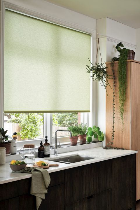 Marble and wood kitchen with a light-green blind and hanging plants