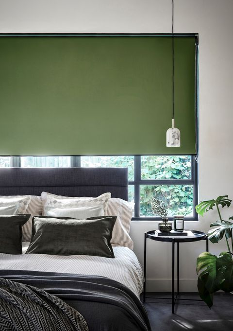 Monochrome bedroom with a dark green blind and plants fitting the colour theme