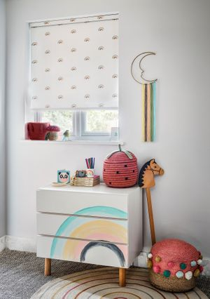 A colourful, rainbow themed bedroom with a white and rainbow-print blind