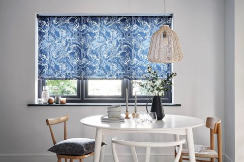 A monochrome dining room with a marble blue blind and wooden furniture