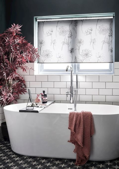 A striking monochrome bathroom with a neutral floral blind and blush pink highlights from the furnishings