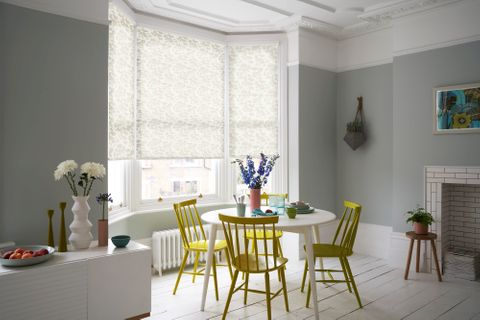 A neutral blue dining room with white and muted yellow, floral, bay-window blinds and striking yellow furniture