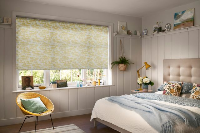 A warm bedroom with a white and yellow blind and neutral furnishings