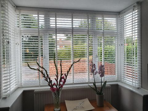 White faux wood blinds in dining room bay window