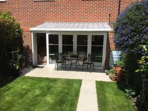 Grey Awning installation above back garden patio doors