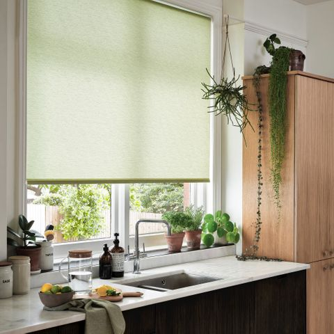 Conscious Lime roller blind made of recycled polyester displayed in a kitchen surrounded by greenery of plants and the kitchen sink