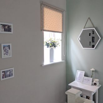 Small pink roller blind in hallway window with white accessories