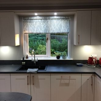 A tree-print, grey and white roller blind in a modern, monochrome kitchen