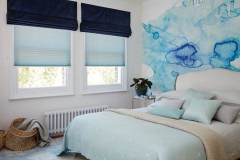 Dark blue velvet roman blind over light blue pleated blinds in a white bedroom with blue accents