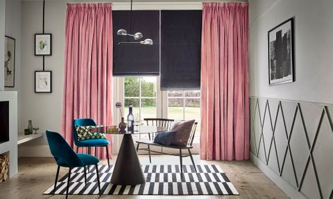 Velvet, rose pink curtains over a dark roman blind in a modern living room