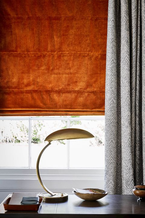 Burnt orange velvet roman blind under grey, patterned curtains in a modern study space