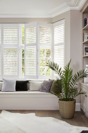 Richmond Silkwhite Shutters in a lounge window with white furniture