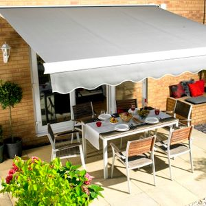 Grey Garden Awning with scalloped hem hanging over a patio table set for dinner