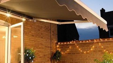 A grey awning hanging over a table set for dinner in the evening, with fairy lights twinkling in the background