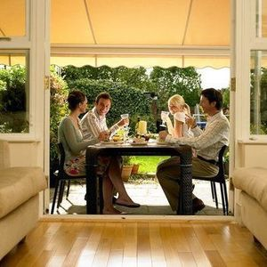Yellow awning with scalloped hem shielding the sun off a group of people dining al fresco