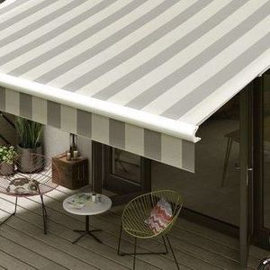 A grey-striped awning hanging over patio furniture on a bright day