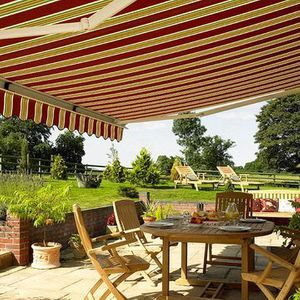 A red striped awning with scalloped hem hanging over a bright garden and patio furniture