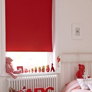 Bright red Acacia Pillerbox roller blind hung in bedroom