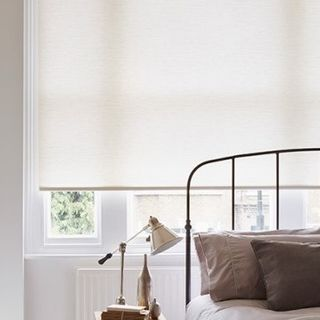 Plain Norfolk Ivory roller blind hung in bedroom