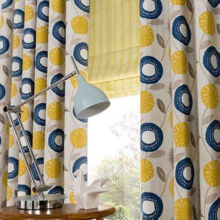 Blue and yellow patterned made to measure curtains combined with a yellow striped roman blind in the living room - Freyja Mustard curtains and Lotta Citron Roman Blinds