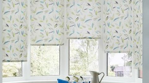 Floral patterned Joya Yellow roller blinds hung in dining room