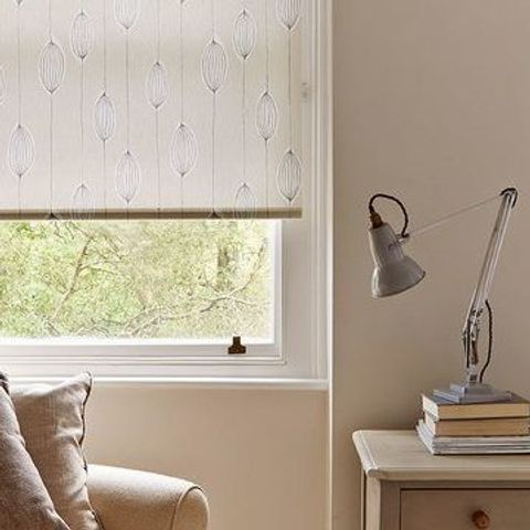 Silas Natural roller blind with seed head design hung in study