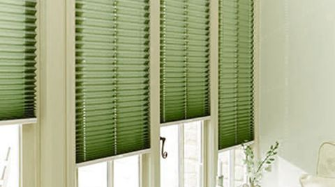 Green coloured pleated blinds fitted to a series of tall and thin windows with cream coloured frames