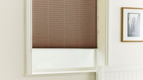 Grenoble chocolate pleated blinds fitted to a square shaped window in a bedroom decorated in a cream colour
