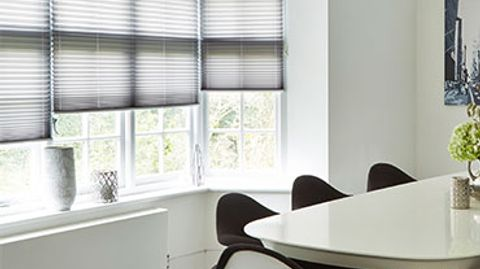 Grey coloured pleated blinds are fitted to a bay window in a dining room that is decorated in white