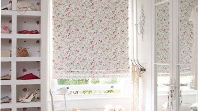 A white roman blind decorated with the bright colours and patterns of birdsong summer which is fitted to a rectangular shaped window in a bedroom that is decorated in white