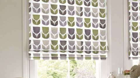 Roman blind decorated with a repeating floral design in green, dark grey and light grey which is fitted to a tall rectangular window in a bedroom